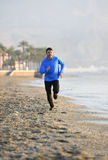 Homem novo do esporte que corre no exercício da aptidão na praia ao longo do amanhecer do mar Foto de Stock