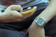 Homem novo do estilo de vida que usa um telefone celular com mensagem texting Imagem de Stock