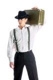 Homem novo do gângster que prende uma mala de viagem velha Fotografia de Stock Royalty Free