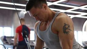 Homem novo do halterofilista que faz o exercício para o tríceps no gym vídeos de arquivo