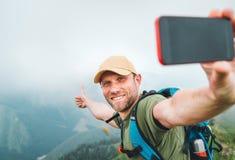 Homem novo do mochileiro que toma a imagem do selfie usando o smartphone e mostrando os polegares acima durante o passeio pelo te imagens de stock royalty free