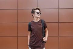 Homem novo do moderno à moda americano em um t-shirt à moda em óculos de sol pretos com um penteado elegante com imagem de stock royalty free