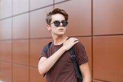 Homem novo do moderno à moda americano em um t-shirt à moda marrom em óculos de sol escuros com um penteado na moda com foto de stock