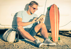 Homem novo do moderno com a tabuleta que senta em seguida seu carro fotos de stock