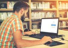 Homem novo do moderno do negócio que trabalha em seu portátil Foto de Stock Royalty Free