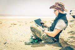Homem novo do moderno que senta-se na estrada do deserto - conceito da tecnologia fotografia de stock