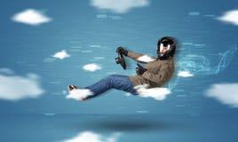 Homem novo do racedriver engraçado que conduz entre o conceito das nuvens Foto de Stock