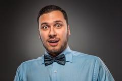 Homem novo do retrato na camisa azul, olhando com perplexidade Fotos de Stock Royalty Free
