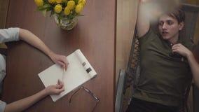 Homem novo do retrato que encontra-se em um berço no escritório de um psicólogo, dizendo lhe sobre seus problemas Psic?logo f?mea vídeos de arquivo