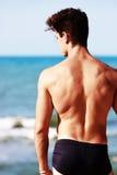Homem novo do traseiro olhando o mar Fotografia de Stock Royalty Free