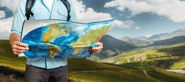 Homem novo do viajante com o mapa de exploração da trouxa nas montanhas Caminhando o conceito da viagem do turismo foto de stock
