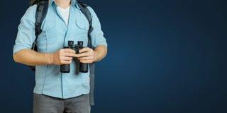 Homem novo do viajante com trouxa e binóculos que procura o sentido no fundo azul Caminhando o conceito da viagem do turismo imagens de stock