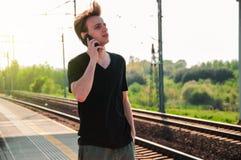 Homem novo do viajante que fala atrav?s do telefone na esta??o de trem durante o tempo quente do ver?o, fazendo gestos ao falar imagens de stock royalty free