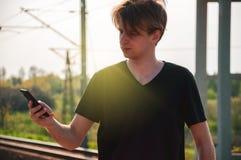 Homem novo do viajante que fala atrav?s do telefone na esta??o de trem durante o tempo quente do ver?o, fazendo gestos ao falar fotografia de stock