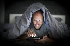 Homem novo do viciado do telefone celular acordado tarde na noite na cama usando o smartphone foto de stock
