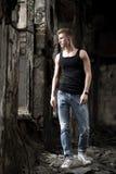 Homem novo do yog do retrato na camisa e nas calças de brim que estão no fundo abandonado Foto de Stock Royalty Free