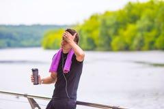 Homem novo dos esportes com toalha e garrafa da água Fotografia de Stock Royalty Free