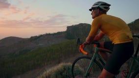 Homem novo dos esportes que senta-se em uma bicicleta em uma parte superior da montanha em um capacete e em um material desportiv video estoque