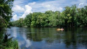 Homem novo dos pares e fotógrafo da mulher que kayaking abaixo de Santa Fe River em Florida em um caiaque amarelo com uma florest imagem de stock royalty free