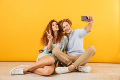 Homem novo dos pares otimistas e mulher 20s que sentam-se no toget do assoalho imagem de stock