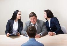 Homem novo durante a entrevista de trabalho e os membros dos managemen fotografia de stock royalty free