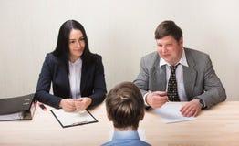 Homem novo durante a entrevista de trabalho e os membros dos managemen imagem de stock