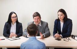 Homem novo durante a entrevista de trabalho e os membros dos managemen fotografia de stock