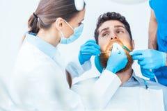Homem novo durante um procedimento oral indolor no escritório dental foto de stock royalty free