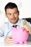 Homem novo e banco piggy Fotos de Stock