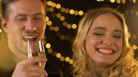Homem novo e champanhe bebendo fêmea e riso, tendo o bom tempo no partido vídeos de arquivo