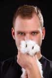 Homem novo e coelho doméstico no fundo preto Imagem de Stock Royalty Free