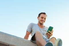 Homem novo e considerável com assento móvel do smartphone foto de stock royalty free