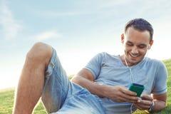 Homem novo e considerável com smartphone móvel imagem de stock