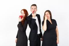 Homem novo e duas mulheres no preto em um fundo branco fotos de stock royalty free