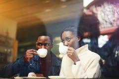 Homem novo e estudantes de mulher que bebem bebidas quentes ao descansar após leituras na universidade fotos de stock royalty free