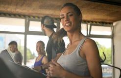 Homem novo e exercício das mulheres no gym imagem de stock royalty free