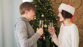 Homem novo e menina que falam e que sorriem com os vidros do champanhe que estão perto da árvore de Natal Modo do Natal video estoque