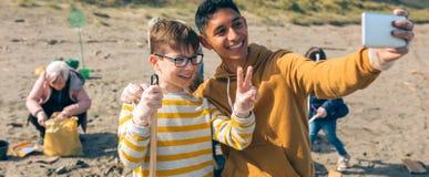 Homem novo e menino que tomam o selfie ao grupo de volunt?rios que limpam a praia foto de stock