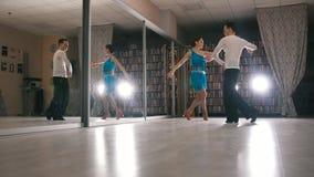 Homem novo e mulher atrativos que dançam e que ensaiam a dança latino-americano nos trajes no estúdio video estoque