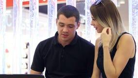Homem novo e mulher bonita que trabalham em um portátil video estoque