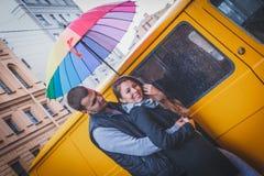 Homem novo e mulher com o cabelo longo que abraça sob um guarda-chuva colorido brilhante que sorriem na perspectiva da camionete  Imagens de Stock