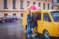 Homem novo e mulher com o cabelo longo que abraça sob um guarda-chuva colorido brilhante que sorriem na perspectiva da camionete  Imagem de Stock Royalty Free