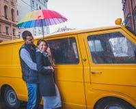 Homem novo e mulher com o cabelo longo que abraça sob um guarda-chuva colorido brilhante que sorriem na perspectiva da camionete  Imagem de Stock