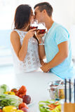 Homem novo e mulher com vinho tinto que beijam na cozinha Imagens de Stock