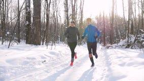 Homem novo e mulher da floresta do inverno que correm na fuga no parque da manhã Luz solar bonita vídeos de arquivo