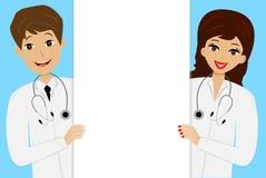 Homem novo e mulher de dois doutores no fundo azul Fotografia de Stock Royalty Free