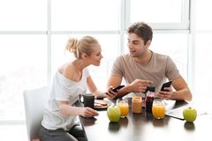 Homem novo e mulher de sorriso que falam um com o otro quando tenha o café da manhã foto de stock