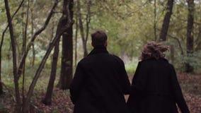 Homem novo e mulher dos pares que correm no movimento lento da floresta do outono video estoque
