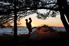 Homem novo e mulher dos pares que têm o resto na barraca do turista e em fogueira ardente na costa de mar perto da floresta fotografia de stock royalty free