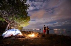 Homem novo e mulher dos pares que têm o resto na barraca do turista e em fogueira ardente na costa de mar perto da floresta fotografia de stock